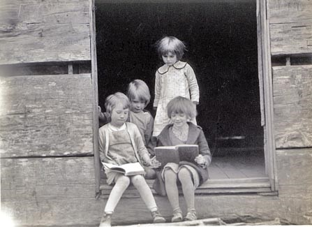 Historic photo of 4 young girls sitting and standing in the doorway of a log schoolhouse