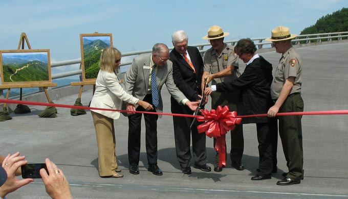 A group of officials cut the ribbon on the newly completed bridge.