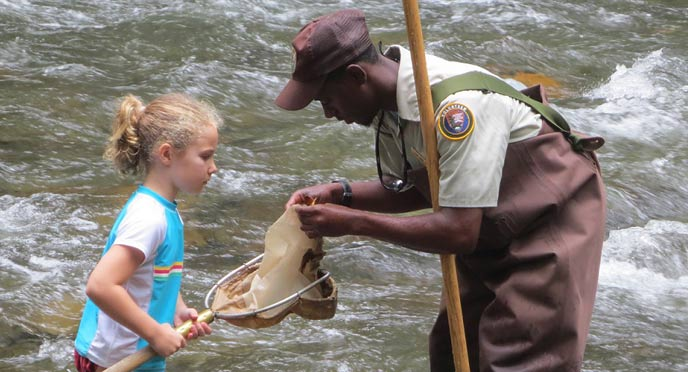A high school intern netting aquatic invertebrates with a young park visitor