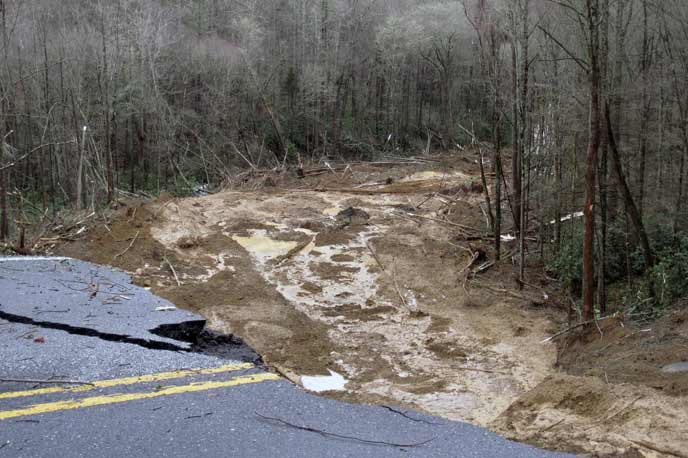 Both lanes of road are washed out with a river of water running where the road used to be