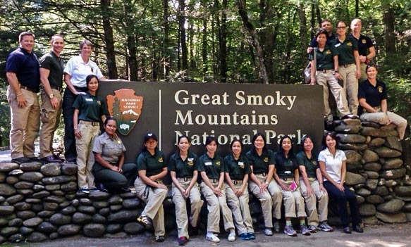 NPS, Cambodian, and Thai park staff pose at the entrance sign to Great Smoky Mountains National Park