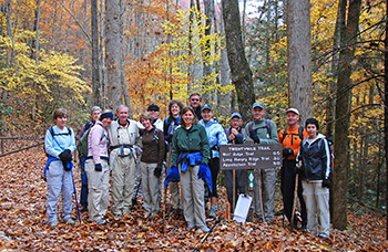 A group of hikers posing beside a wooden trail sign. Colorful fall foliage surrounds the group.