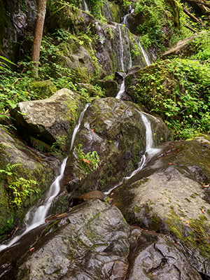 Water trickles around boulders on a rock face.