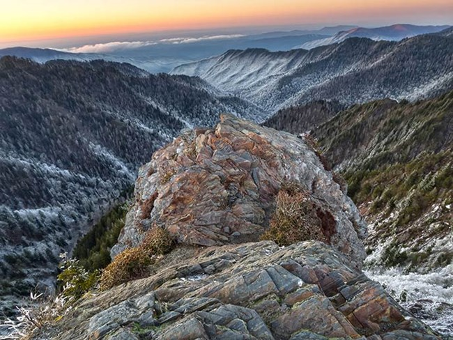 A craggy, rock promontory overlooks snow covered mountains and valleys.