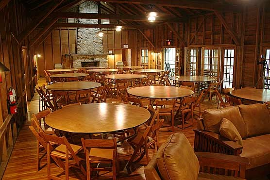 The meeting room is furnished with round tables and folding chairs.