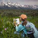 Young girl using a field guide from the Grand Teton Association