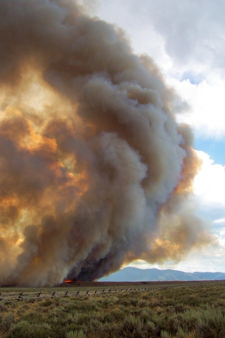 A fire moves across the flat, sagebrush-covered plains, putting up a column of smoke into the air.