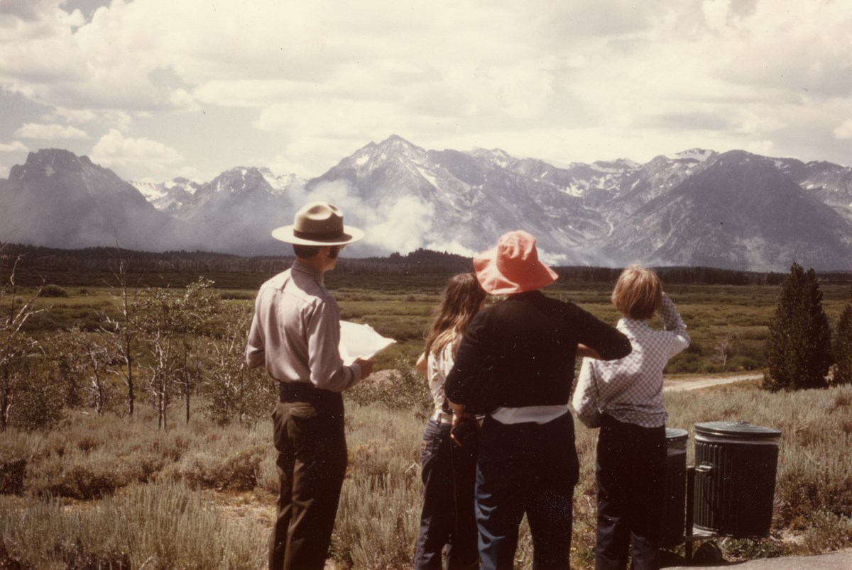 A park ranger talks to three visitors about a fire visible on distant peaks.
