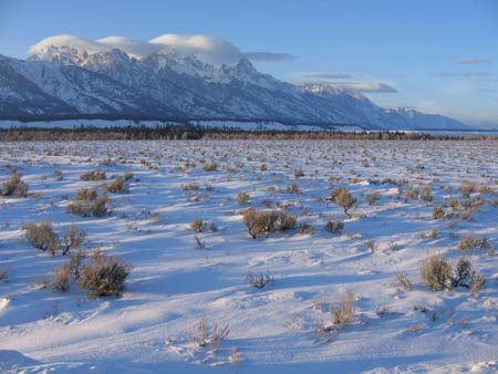 Lenticular clouds hover over the Teton Range, windswept snow and sagebrush in the valley below.