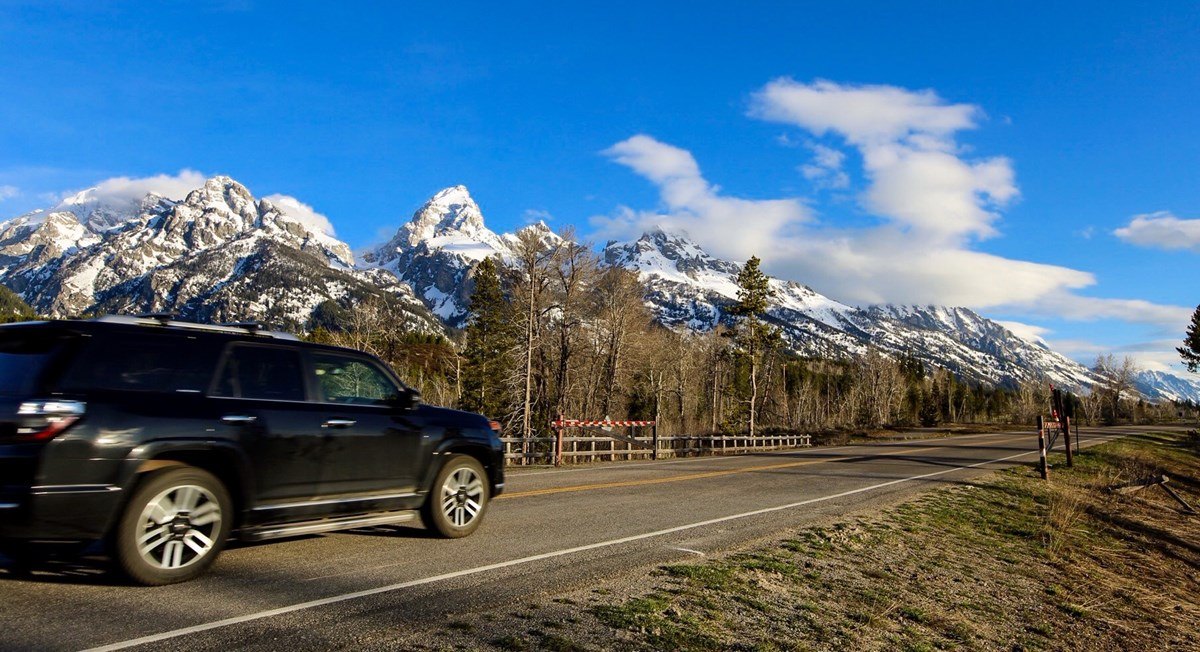 Car driving on road with the Teton Range in the distance