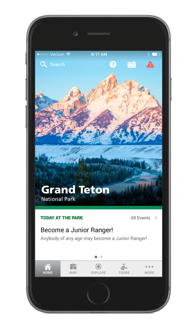 Grand Teton app home screen on smartphone. Home screen of app has image of craggy Teton mountains at sunrise with pink and light blue tones with the snake river in the foreground.  An events box sits near the bottom with a button bar at the bottom.