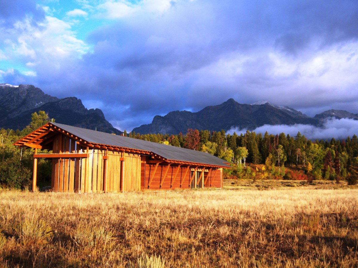 A wood building with mountains in the background.