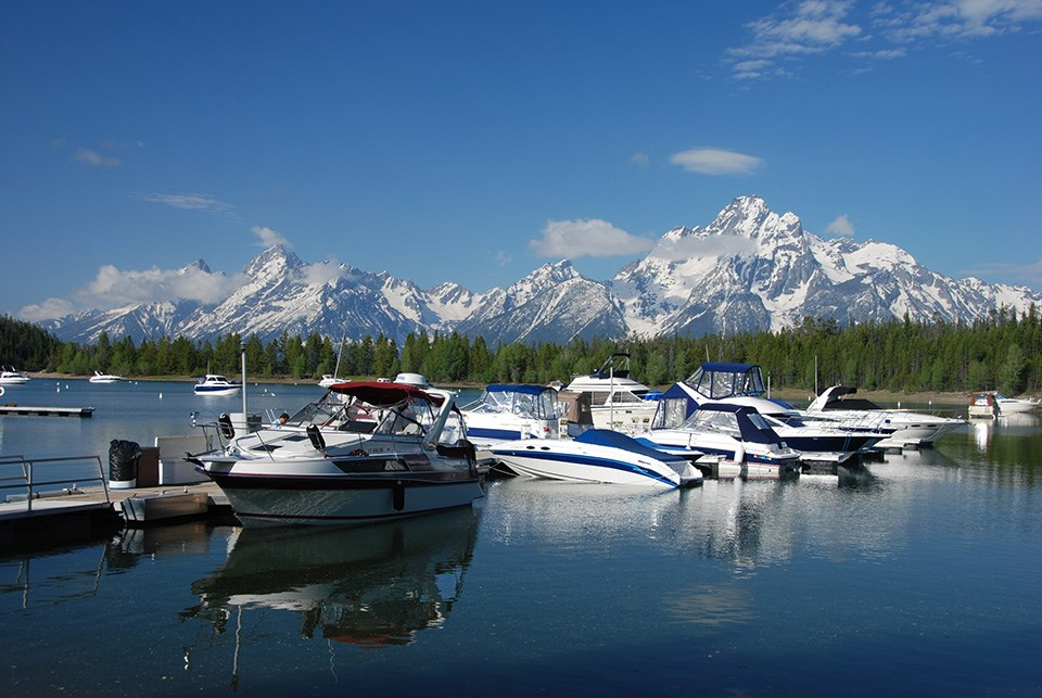 Boats moored to the dock at the Colter Bay Marina with Mount Moran across Jackson Lake in the distance.