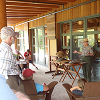 Ranger presentation about beaver on front porch with visitors.