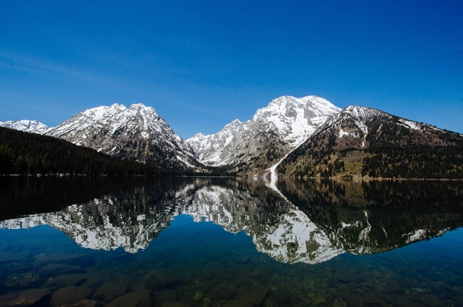 Snowy mountains reflected on a glassy lake.