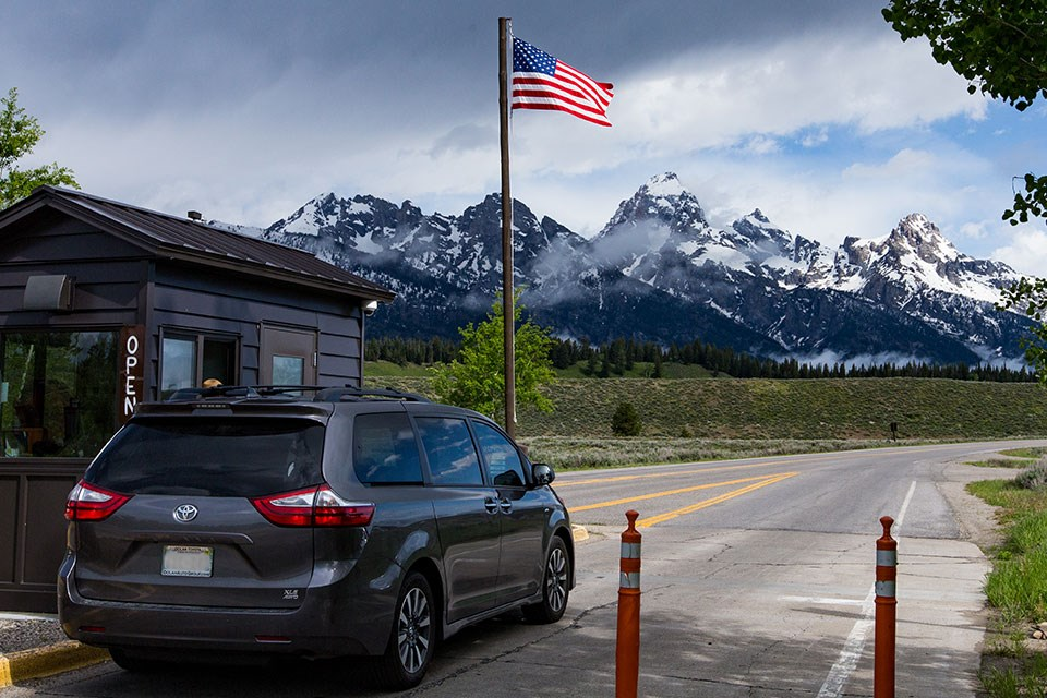 Car at Entrance Station with American Flag on a pole and the Teton Range in the distance