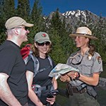 Two park visitors talking to a park ranger