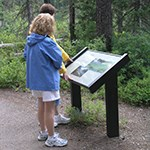 Visitors reading a park sign