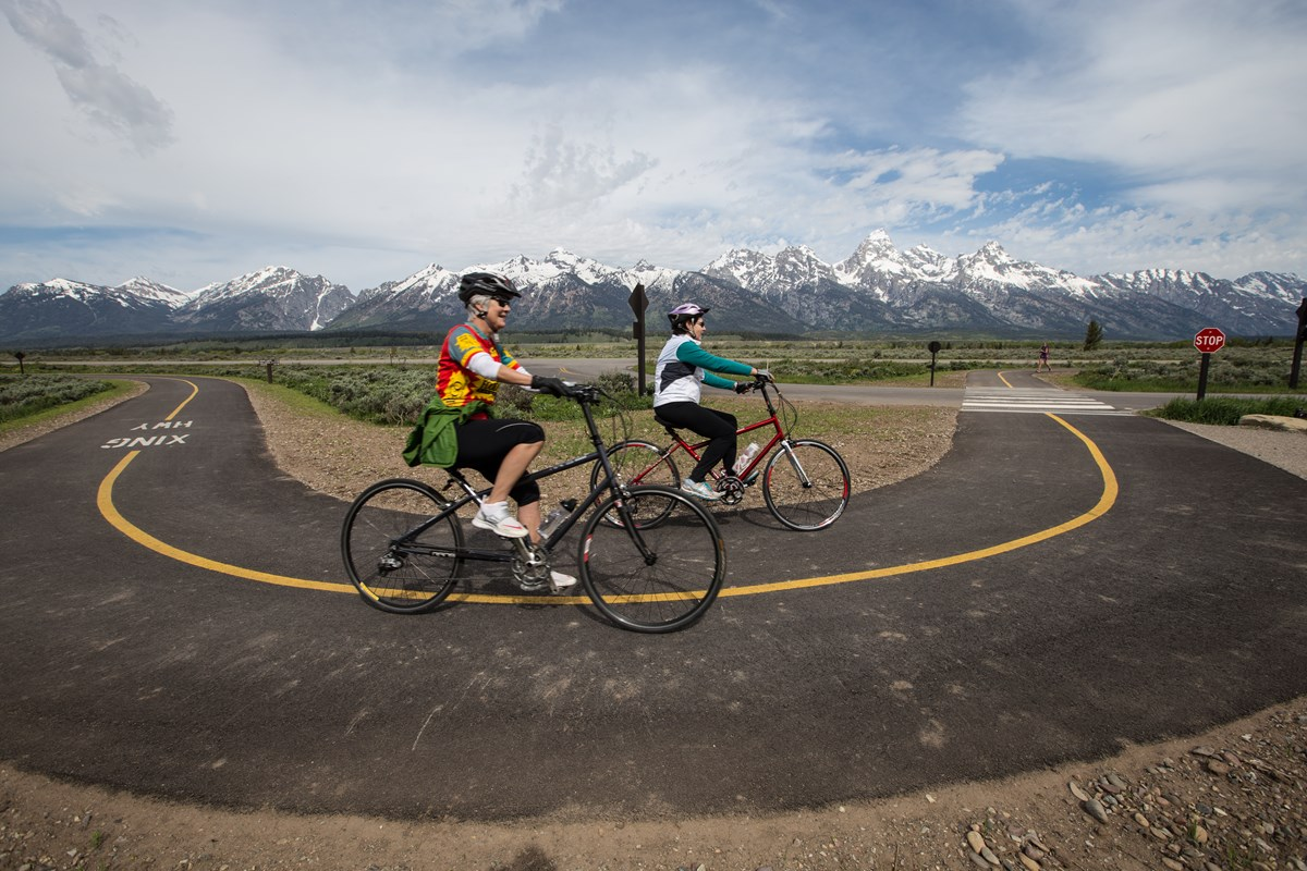 Two bikers ride around a curve on a paved path with mountains in the background.