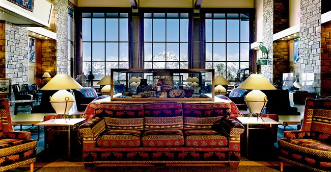 A hotel lobby with mountains viewed through the windows.