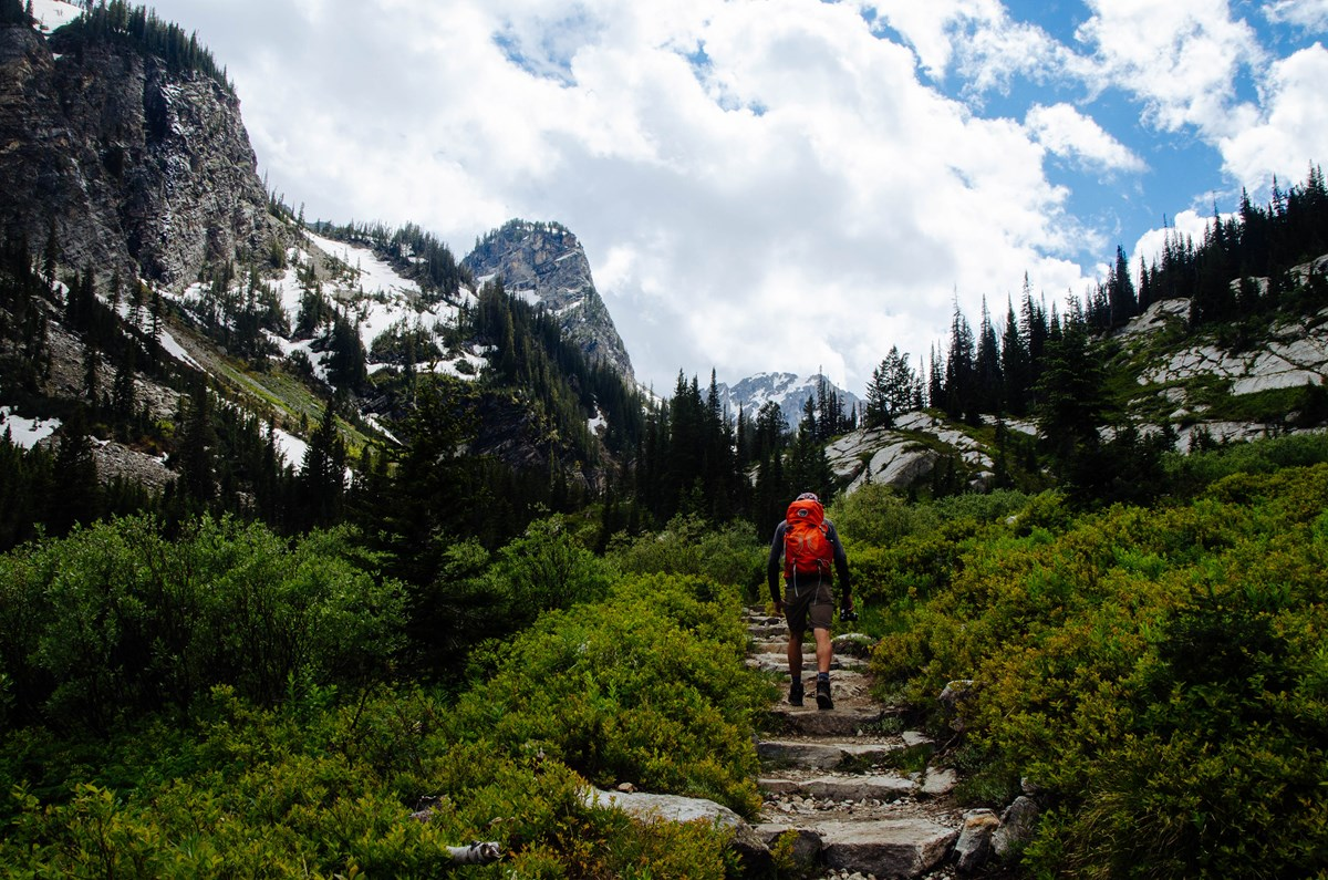 A hiker walks up a trail in a mountain canyon.