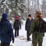 A ranger leading visitors on snowshoes