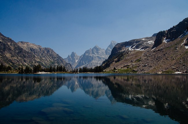 The Grand Teton and Mount Owen are reflected on an alpine lake.
