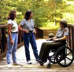 Two park visitors talking to a ranger in a wheelchair