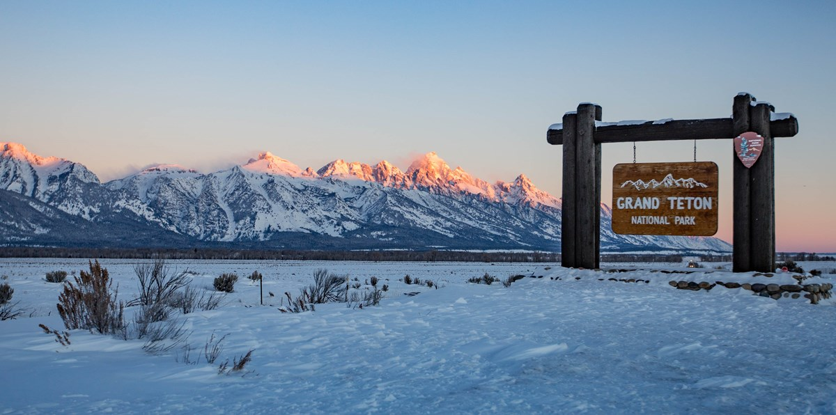 "A snowy mountain range behind a sign reading ""Grand Teton National Park""."