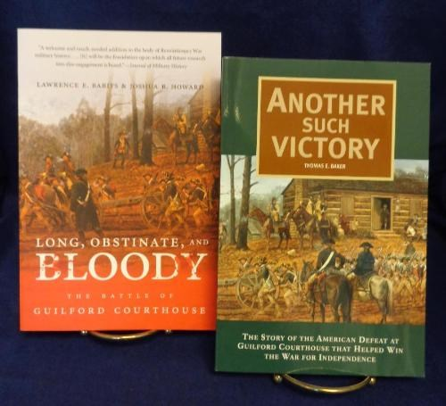 "Book covers ""Long, Obstinate, and Bloody"" is red with a watercolor painting of the 18th century courthouse and battle and ""Another Such Victory"" is green with the same image of the 18th century courthouse - both feature cannons and men on horses"