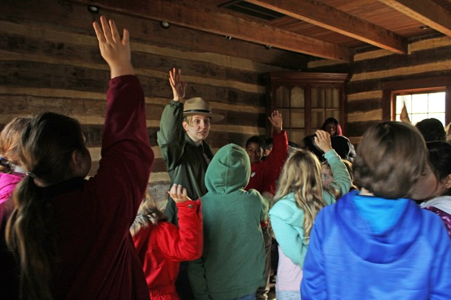 Park Ranger and students raise hands inside a historic log house