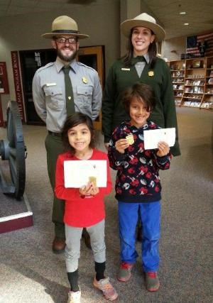 Two park rangers stand behind two new junior rangers holding their badges