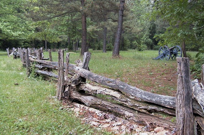 Split rail fence, six-pounder cannon on a forested battlefield