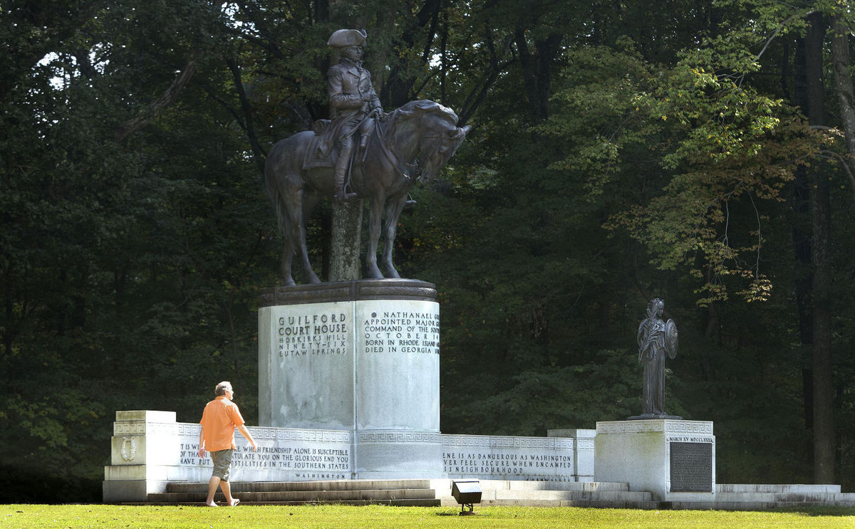 Man in orange shirt walks in front of the equestrian monument to Maj. General Nathanael Greene