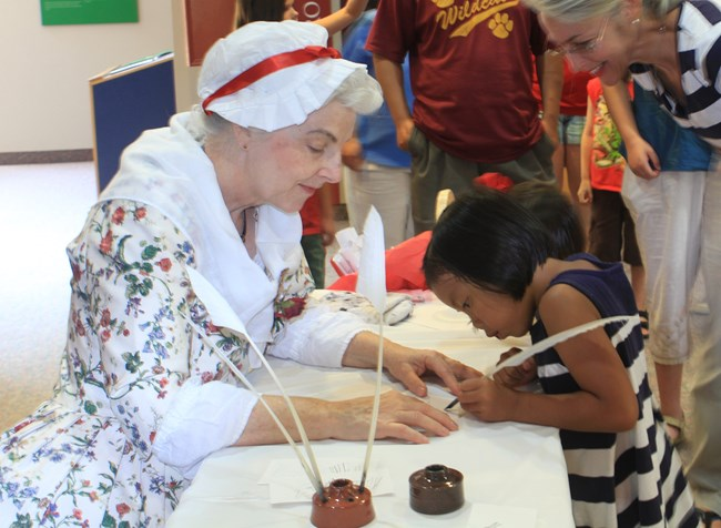 Living History Interpreter woman teaches child how to write with a quill pen