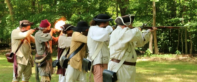 Six men in colonial living history militia point muskets to fire at woods