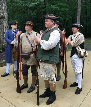 Living history militia group stand with black powder muskets