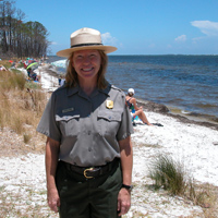A female ranger stands in front of beach users at the Naval Live Oaks Area.