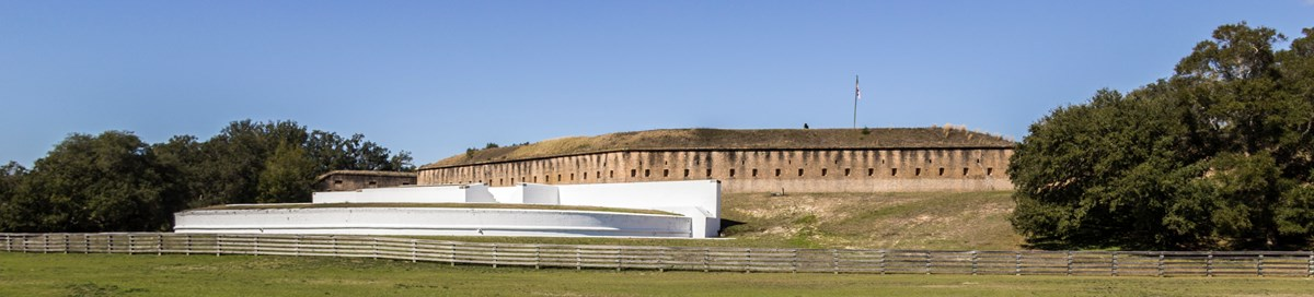 Two large masonry forts stand on a hill below a blue sky