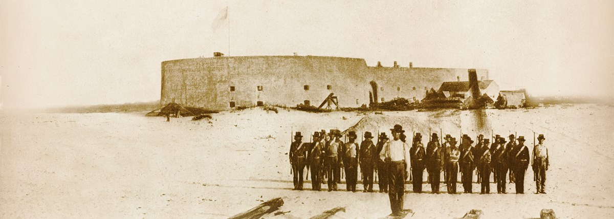 Historic image of soldiers standing in front of a masonry fort.