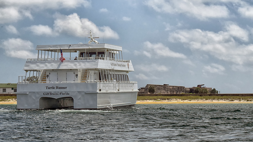 A large white ferry boat sits offshore of a historic brick fortification.