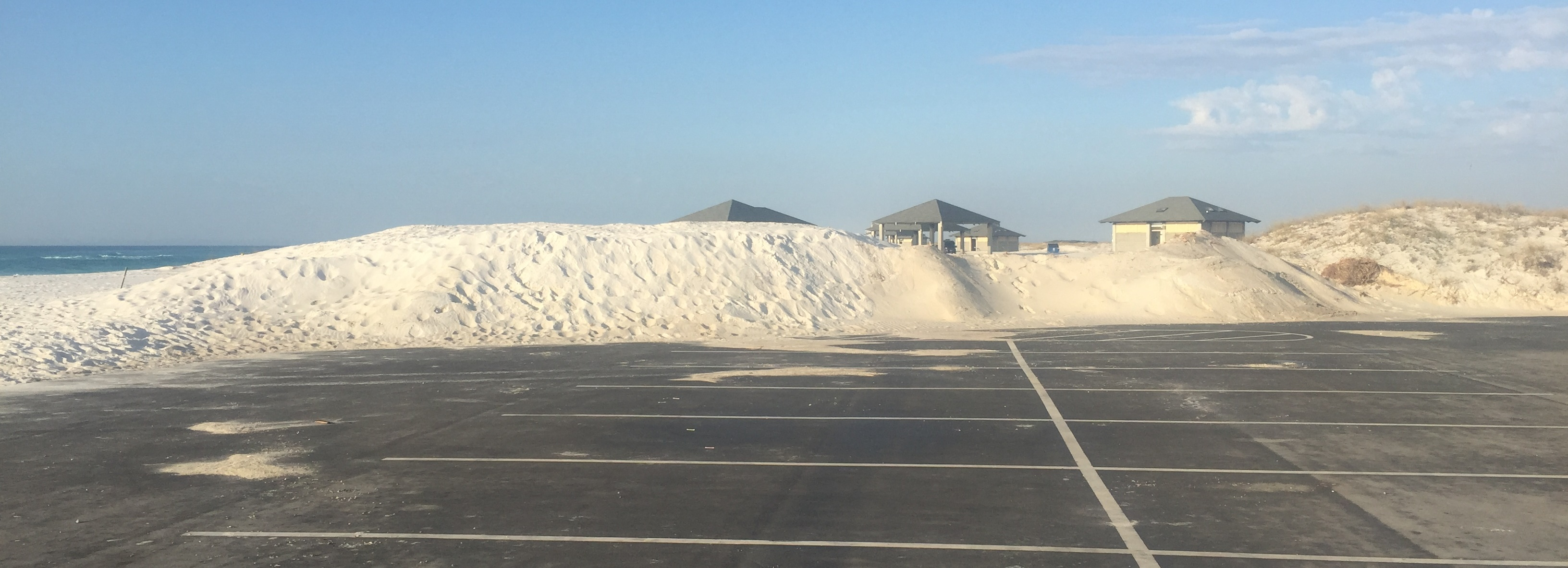 Mounds of white sand stand at the edge of a paved area. Pavilion roofs can be seen in the distance.