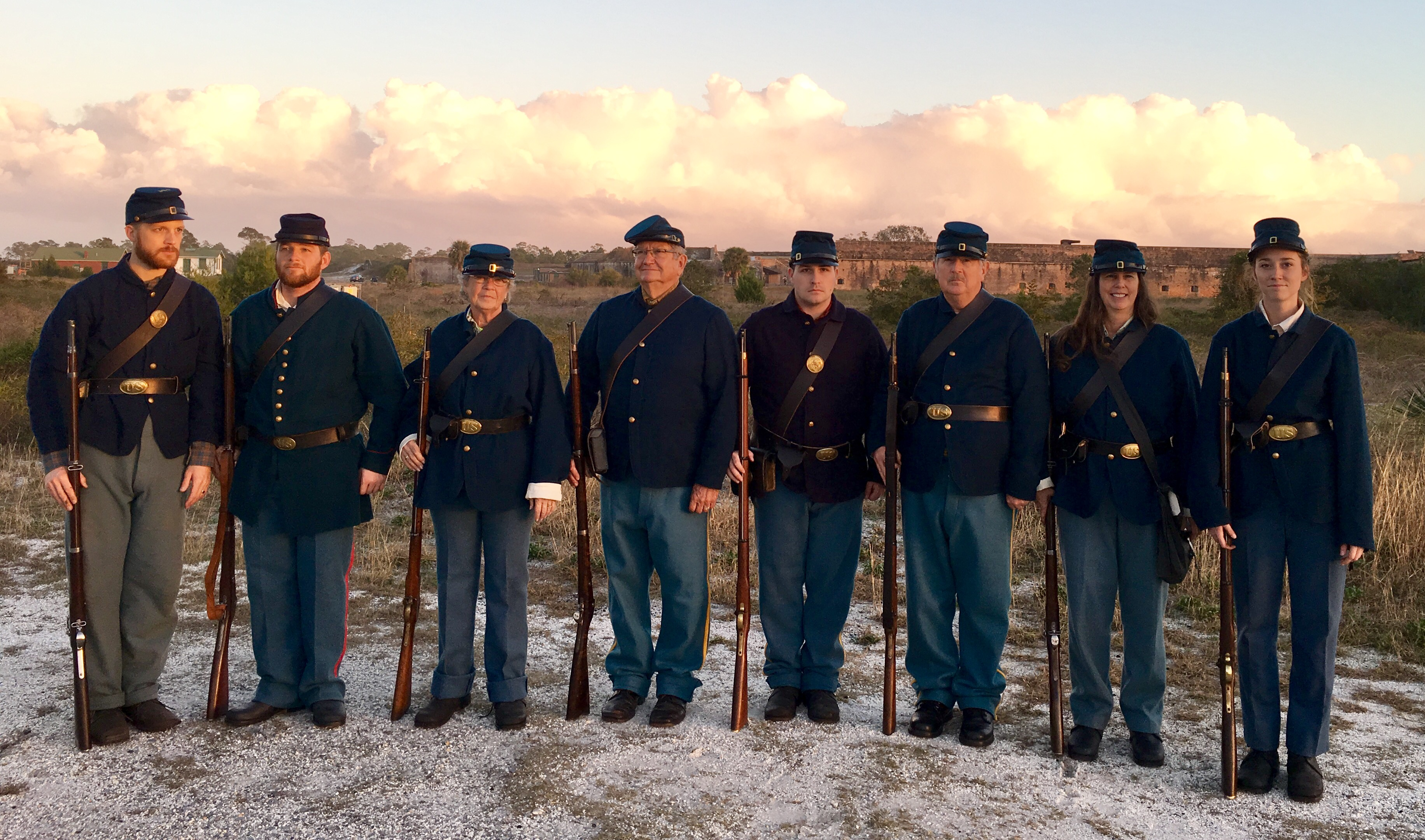 Eight people stand shoulder to shoulder in Civil War era uniforms