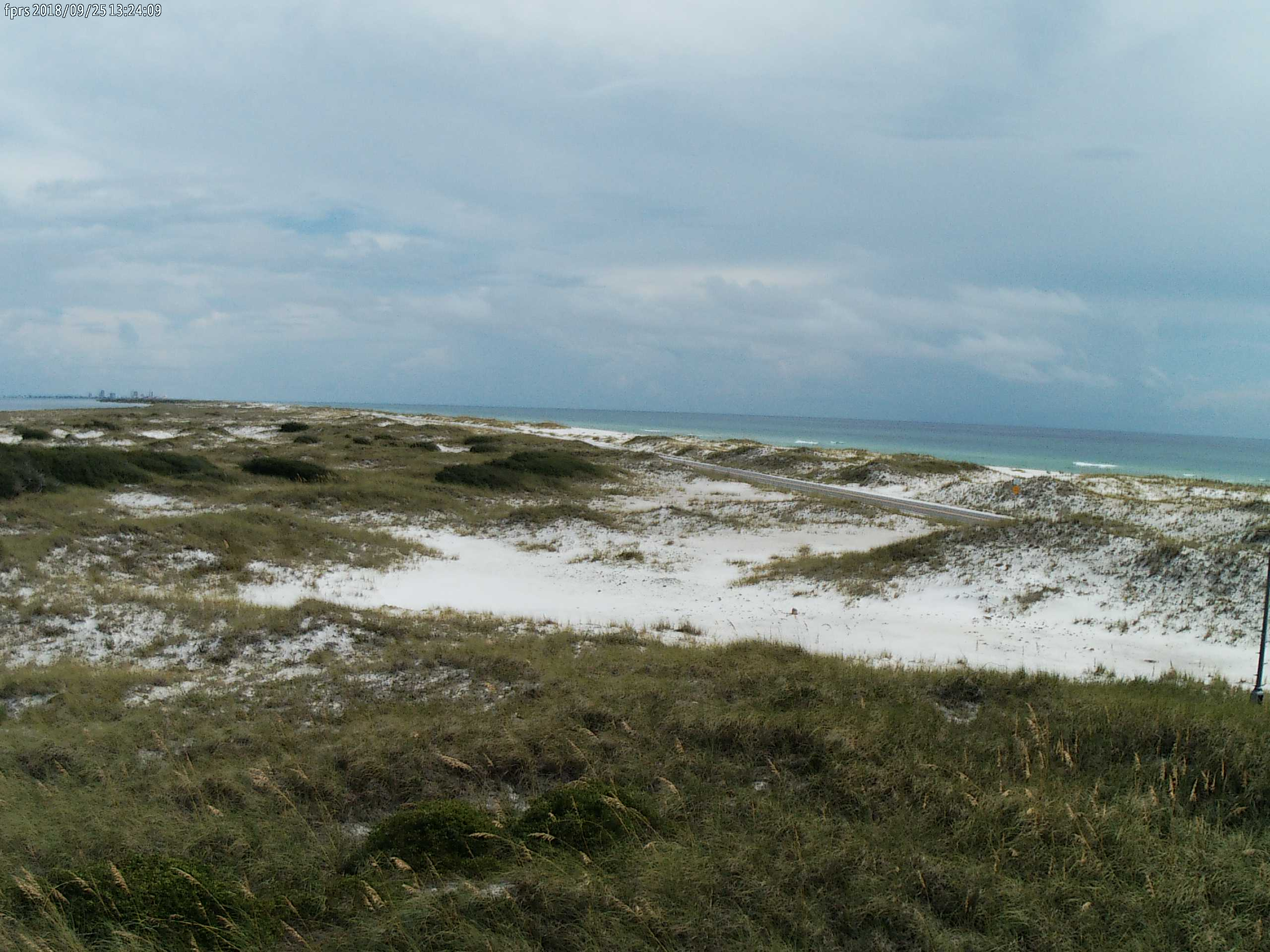 A daytime beach scene showing white sands, vegetation covered dunes, and emerald green waters in the background.