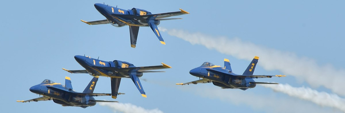 Four blue and yellow fighter jets, two inverted, fly in close formation.