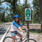 A female visitor on her bike is next to the Live Oaks Bicycle Route sign.