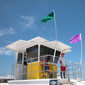 A national park lifeguard stands at the lifeguard tower while two safety flags fly in the wind.