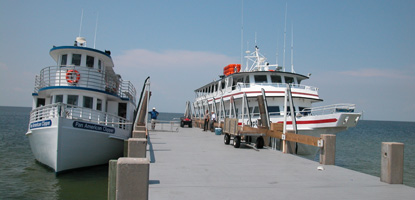 Two passenger ferries, Pan American Clipper and Captain Pete, are docked at the West Ship Island pier on a clear, sunny summer day.