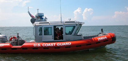 The bright orange U. S. Coast Guard vessel patrols the coastline.