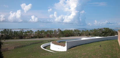A view of the white-washed Spanish Water Battery at Fort Pickens with blue sky and white puffy clouds in the background.